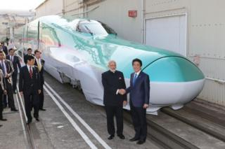 "This file photo taken on November 12, 2016 shows India""s Prime Minister Narendra Modi (2nd R) and his Japanese counterpart Shinzo Abe (R) shaking hands in front of a Shinkansen train during their inspection of a bullet train manufacturing plant in Kobe, Hyogo prefecture"