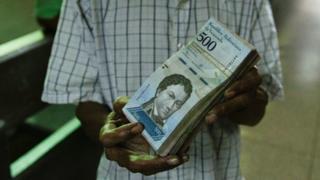 A man holds 500-bolivar banknotes in Caracas, Venezuela, 16 January 2017