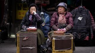 Two currency exchange vendors sit before their stalls as they wait for customers at a market in Seoul