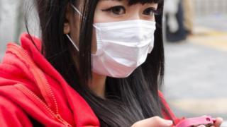 Una joven con una mascarilla en la boca y su teléfono celular en la mano