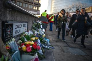 Floral tributes are left near London Bridge for Jack Merritt and Saskia Jones