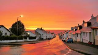 Red Sky reflecting of the rain soaked road Bowmore Islay