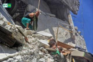 Foto de menina que tenta salvar irmã após bombardeio na Síria