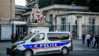 Authorities stand around the statue of Jean-Baptiste Colbert, vandalised by an activist
