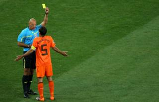 Howard Webb shows a yellow card to Van Bronckhorst in the 2010 World Cup Final in South Africa, between the Netherlands and Spain.