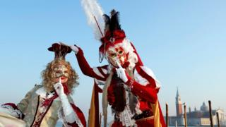 Two masked revellers pose in Venice's Riva degli Schiavoni