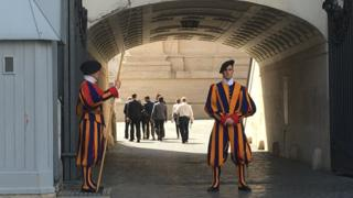 Swiss Guards protect the Vatican as journalists walk to trial
