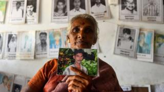 Sri Lankan Tamil woman holds a picture of a missing loved, Missing people organization office