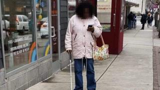 Woman with cane on her phone