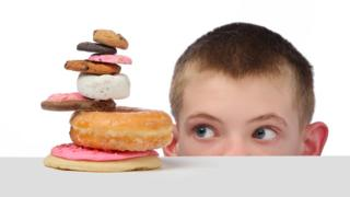 Boy looking at a pile of sugary food