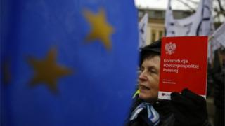 A woman holds a copy of the Polish constitution in front of the Constitutional Court during its session in Warsaw, Poland December 9, 2015