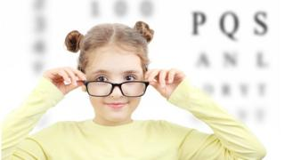 A girl in glasses in front of a row of letters