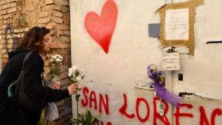 A young woman places flowers at the entrance of a sequestered derelict building in the San Lorenzo district of Rome