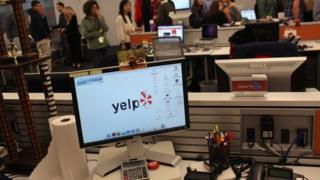 Employees of the online review site Yelp watch as New York City Mayor Michael Bloomberg speaks at the new East Coast headquarters of the tech company on October 26, 2011
