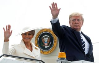 Mr and Mrs Trump waving outside the door to Air Force One