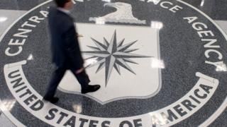 Man walking across a CIA symbol on the floor