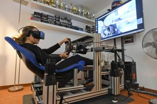 Formula 3 racer Sophia Floersch sits in driving simulator whilst wearing a virtual reality headset