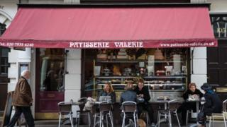 Man walks past Patisserie Valerie