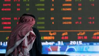 A Kuwaiti trader follows the stock market activity at the Kuwait Stock Exchange (KSE) on 31 December 2015 in Kuwait City