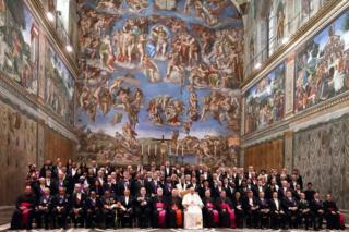 Der Papst und Mitglieder der katholischen Kirche sind in der Sixtinischen Kapelle zu sehen, hinter der sich ein Wandgemälde befindet