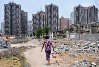 Woman walking through a construction site for more highrise housing in Shanghai, China, on 23 July 2011
