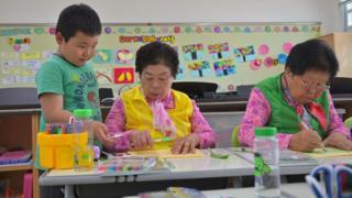 Park Young-ae (C) et Nam Yang-soon (D), avec leur camarade de classe de huit ans (G) à l'école primaire de Woldeung.