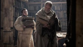A still from the television series Game of Thrones showing two characters in a library