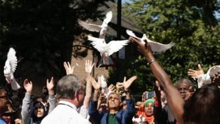 Участники карнавала выпускают голубей