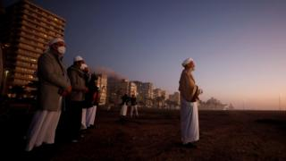 A group of Muslim clerics below a dark sky with buildings in the distance