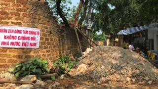 Người dân xã Đồng Tâm ở Mỹ Đức treo khẩu hiệu cạnh đường vào làng bị đổ đất lập ụ ngăn cản giao thông