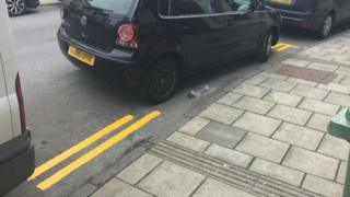 Double yellow lines painted around a black car