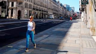 Woman in an otherwise deserted Regent St, London