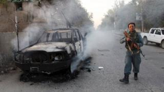 An Afghan policeman next to a burning vehicle, with a gun and the Taliban flag attached, in the city of Kunduz