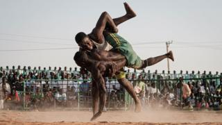 Sudanese wrestlers fight during a traditional Nuba wrestling match at the Haj Youssef stadium in the district of Khartoum on June 21, 2019. - Originating in the Nuba mountains, the sport has become wildly popular country-wide in recent years. The Sudanese Nuba wrestling federation organizes matches every Friday that attract hundreds of people.