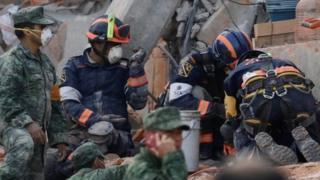 عمال الإنقاذ يستخرجون شيء ما من تحت الأنقاض