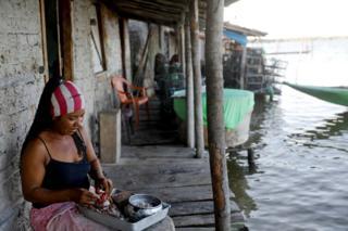 Vandeka, wife of fisherman Jose da Cruz, peels crabs