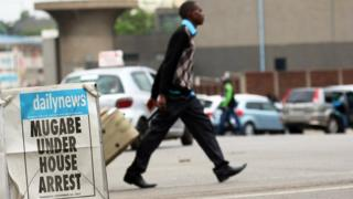 "A man crosses the road in Harare behind a local newspaper poster that reads ""Mugabe under house arrest""."