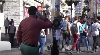 čovek razgovara telefonom naslonjen na banderu