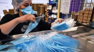 An employee packs protective face masks