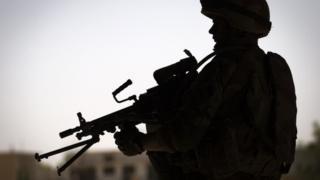 Soldier dey pose with gun