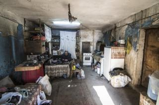A shoemaker sits in his workshop adjacent to his home