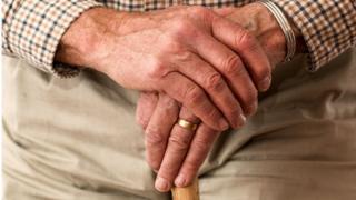 Mãos de um homem idoso, cruzadas uma sob a outra; ele tem uma larga aliança dourada na mão esquerda; veste uma camisa chadrez