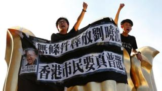 Pro-democracy activists chant slogans on the Golden Bauhinia Square, a gift from China at the 1997 handover, during a protest a day before Chinese President Xi Jinping is due to arrive for the celebrations, in Hong Kong, China 28 June 2017.