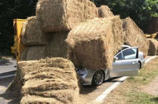 Mercedes car under hay bales