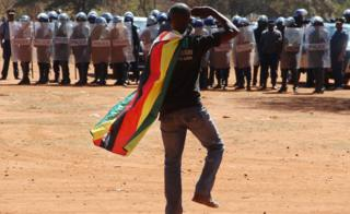 A man wearing a Zimbabwean flag salutes riot police during a protest in Harare, Zimbabwe, on Friday 26 August 2016