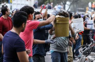 A chain of young men pass buckets of rubble down the line