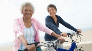 Dos mujeres mayores en bicicletas en una playa