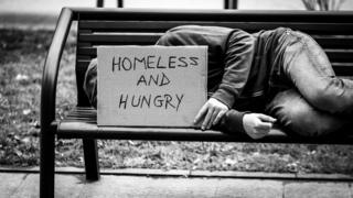 A homeless person lying on a bench with a sign that says homeless and hungry