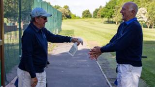 At Filton Golf Club two golfers spray their hands