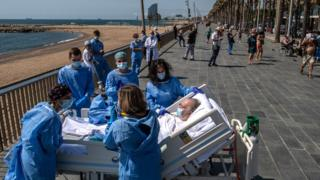 A hospital patient lying in a bed is taken to the seaside by a group of intensive health care staff